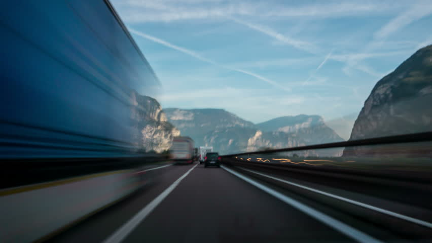 Time Lapse Driver POV motion blur forward driving in Italy countryside road in Dolomite area highway through mountains and valley nature scenic.