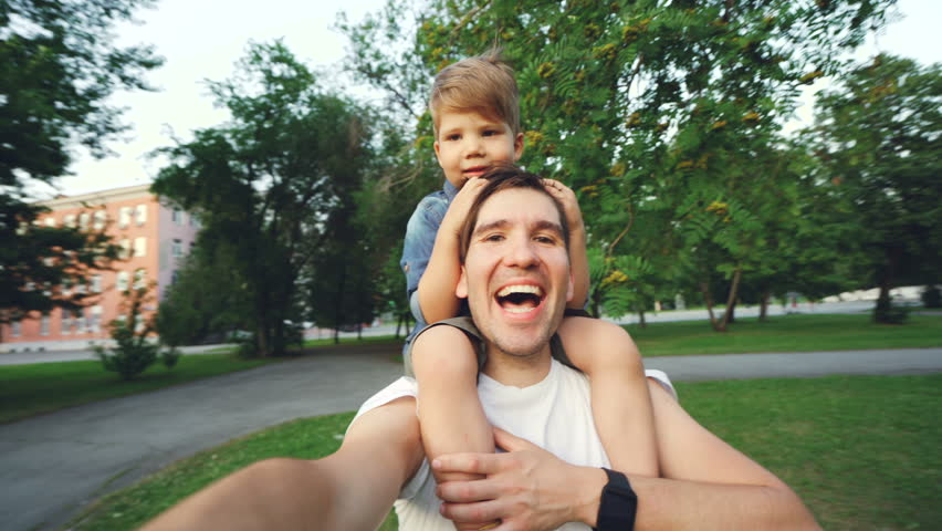 Happy father carrying his smiling son on neck and making video selfie at smartphone camera during walk in park