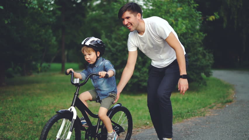 Slow motion of laughing child cycling in park with careful father who is teaching him to ride bicycle. Happy young family, fatherhood and childhood, active lifestyle concept. Royalty-Free Stock Footage #1014435368