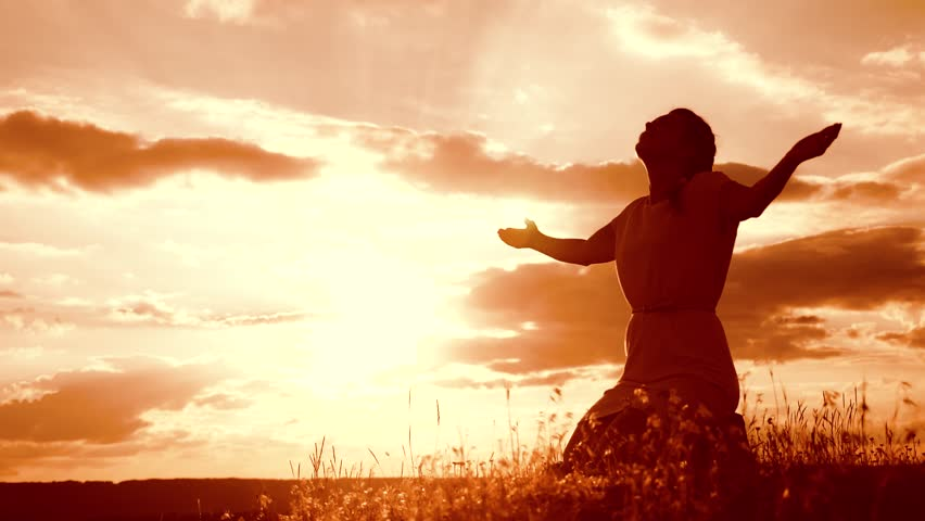 Girl folded her hands in prayer silhouette at sunset. woman praying on her knees. slow motion video. concept Christianity religion catholicism. Girl folded her hands in prayer pray to God. the girl #1014439577