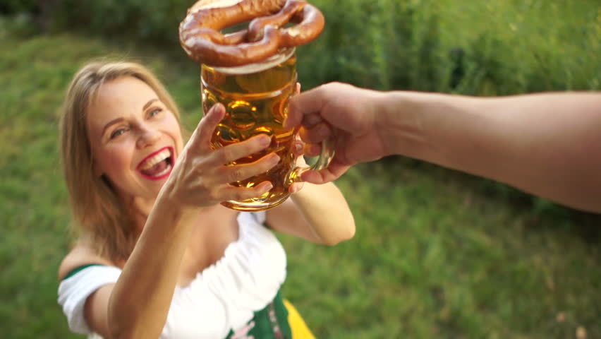 A girl in a traditional Bavarian dress buys beer and pretzel at the Oktoberfest beer festival. A woman laughs cheerfully and enjoys buying. On a green background