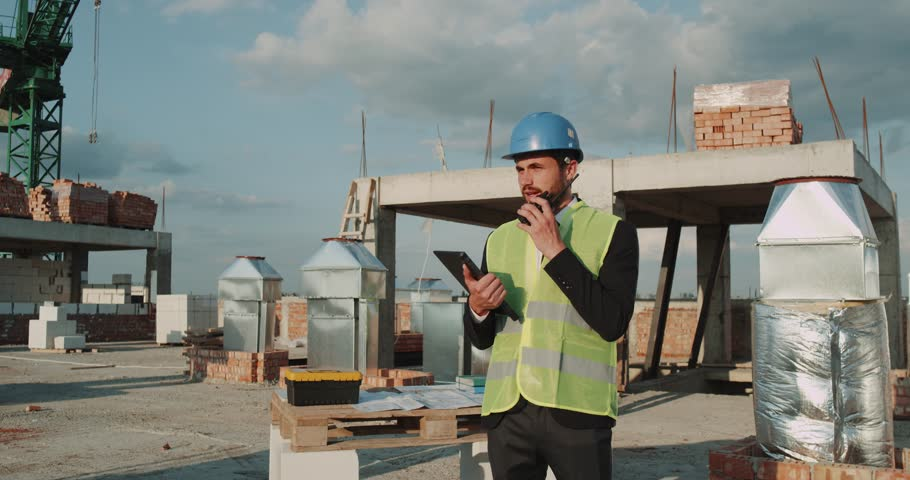 Expert engineer navigate using a tablet and examine unfinished apartment building on rooftop , speaking using a tablet. #1014443750