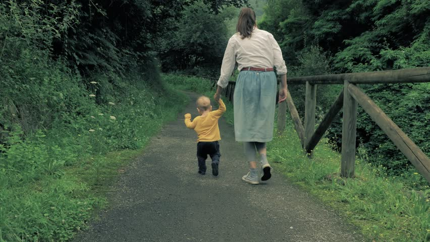4 k slow-motion beautiful young family, mother and son walking along the picturesque scenic contryside peatonal road at the green fairy tale forest | Shutterstock HD Video #1014453131