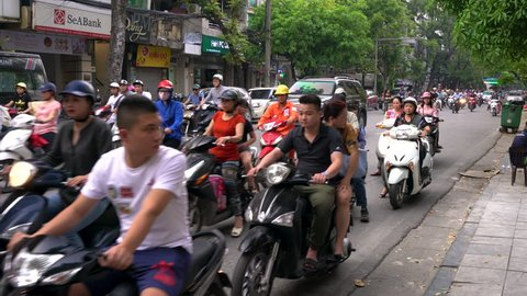 SCOOTERS AND PEOPLE ON THE STREETS OF HANOI, VIETNAM – APRIL 2 2018: Scooters, cars, traffic, tourists, and people on the old quarter streets of the capital city, Hanoi, Vietnam