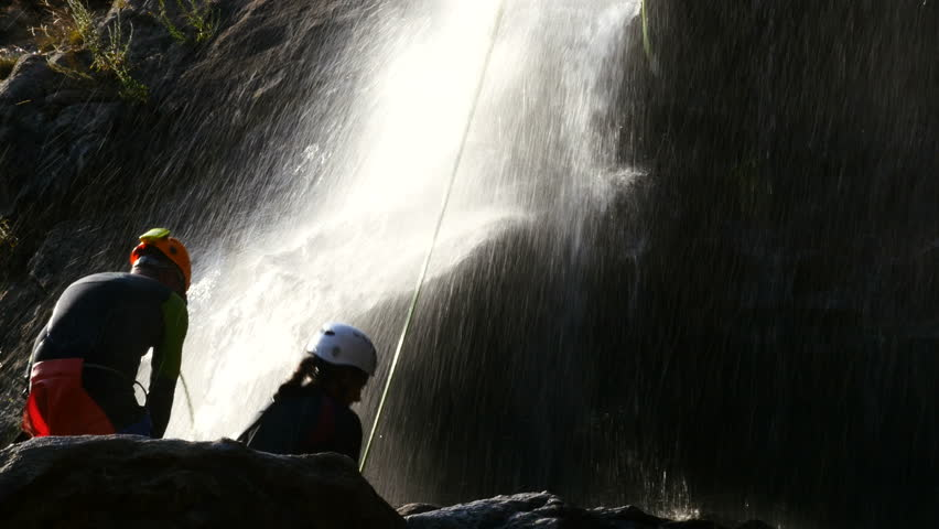 Couple picking up rope after doing canyoning at the Chorrera de los Litueros waterfall at sunset, Puerto de Somosierra, Madrid. Filmed on August 1, 2018. #1014469949