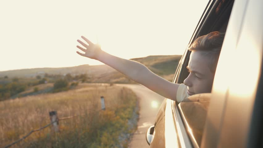 Teen boy looking out the car window and waving his hand. #1014476471