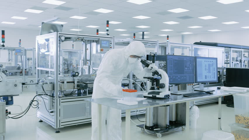 Sterile High Precision Manufacturing Laboratory where Scientists in Protective Coverall's Use Computers and Microscopes, doing Pharmaceutics, Biotechnology and Semiconductor Research