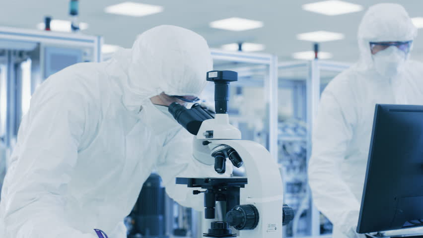 In Laboratory Scientists in Protective Clothes Doing Research, Using Microscope and Entering Data into Personal Computer.