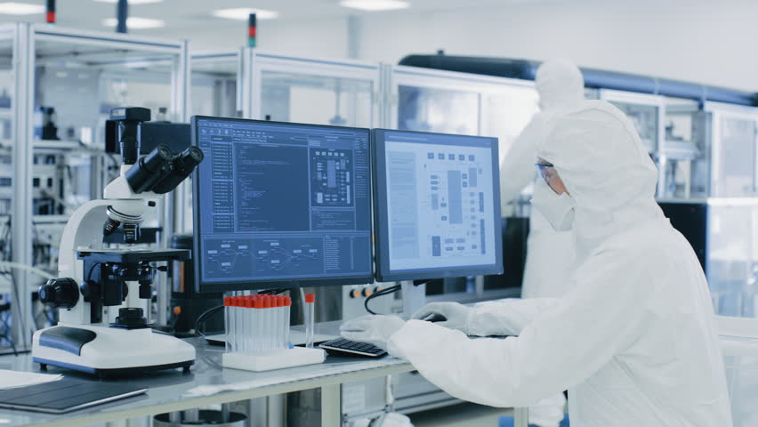 In Laboratory Over the Shoulder View of Scientist in Protective Clothes Doing Research on a Personal Computer. Modern Manufactory Producing Medical Research