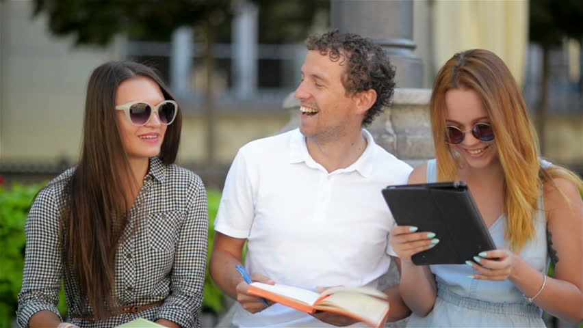 Outdoors Portrait of Three Smiling Students Talking and Studing Together Outdoors Sitting on the Bench. Two Girls and One Man with Notes, Pens and Tablet Spending Time Outside. | Shutterstock HD Video #1014488909