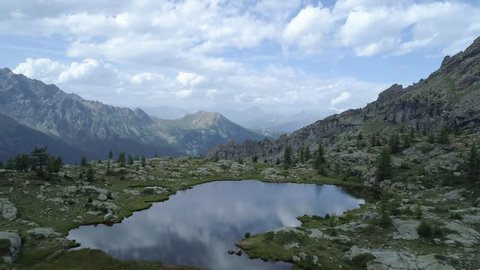 moving forward above clear blue lake and pine woods in evening summer day.Europe Italy Alps Valle d'Aosta outdoor green nature scape mountains wild aerial establisher.4k drone flight establishing shot