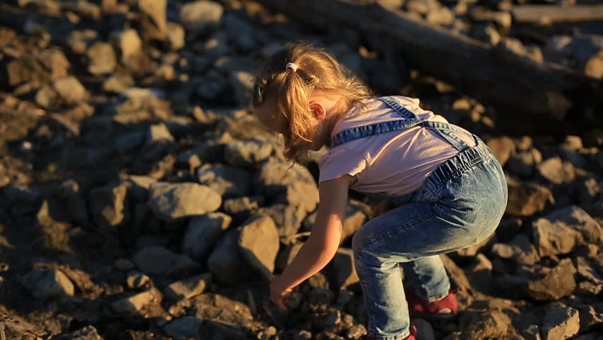 a little girl collects stones on the river and throw them into the water at sunset in the summer evening.
