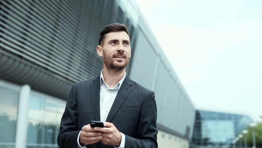 Close up of Young Businessman Walking near the Modern Airport. Looking at his Smartphone's Screen. Classically Dressed. Big Glass Building in the Background. Looking Successful, Confident. #1014544421
