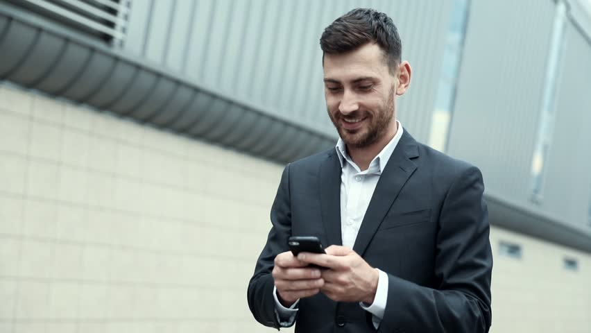 Young Attractive Man Chatting on his Smartphone with Interest. Typing a Message. Walking by the Big Industrial Building. Looking Satisfies. Smiling Sincerly. Classical Jacket. Stylish Clothes. Royalty-Free Stock Footage #1014544424