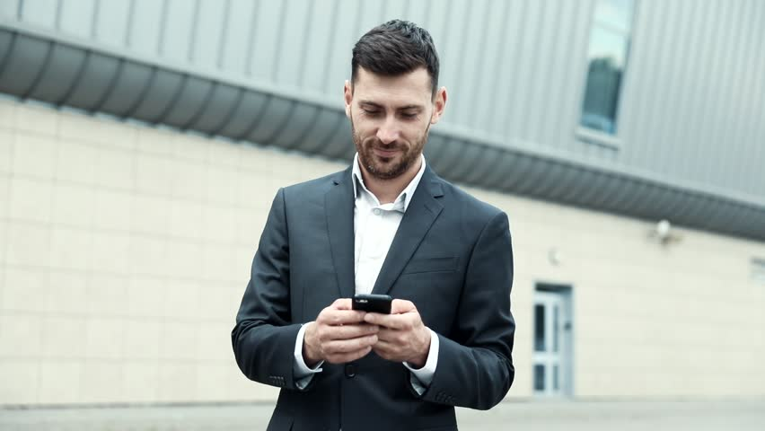 Successful Businessman Standing in the Foreground. Holding Mobile Device in his Hands. Looking on Smartphone's Screen. Young Man Wearing Official Clothes. Classical Jacket. Business Lifestyle. Royalty-Free Stock Footage #1014544442