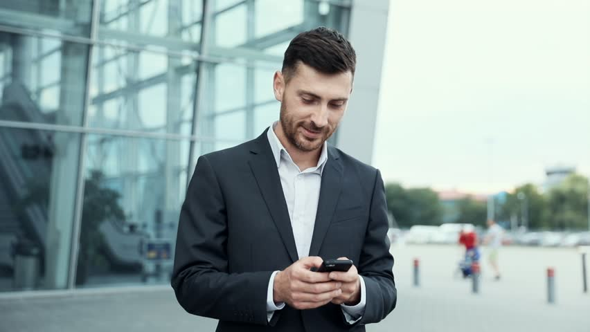 Handsome Businessman Chatting on his Smartphone While Exiting the Big Building. Checking News, Mails.Looking Confident, Successful. Classically Dressed. Walking in the City.