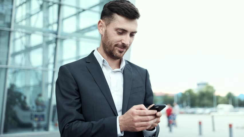 Young Attractive Businessman Standing near Big Modern Office Building. Typing a Message on his Smartphone. Looking Satisfied. Bearded Man Wearing Classical Suit. Business Lifestyle. | Shutterstock HD Video #1014544454