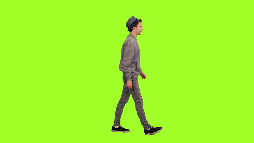 Young stylish man in hat walking on green chroma key background, Side view, 4k pre-keyed footage