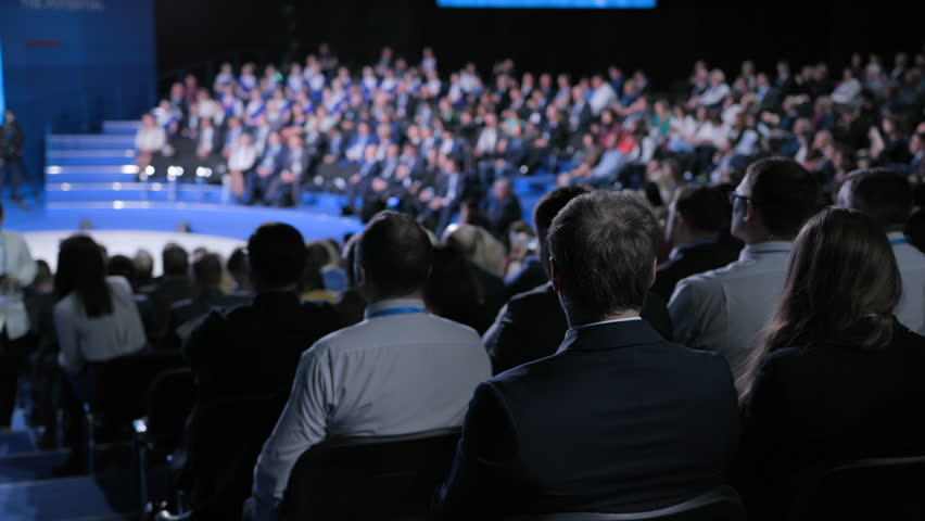 Confident official team at crowded economic forum for strategy education. Concept of male partner or politician at trading briefing indoors. Full row of seats in large place for listener or spectator | Shutterstock HD Video #1014561968
