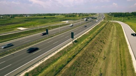 4K. Aerial view on the highway with cars. Highway is filled with cars, trucks and cars leave the city. Highway with dense traffic - tracking shot, natural lighting