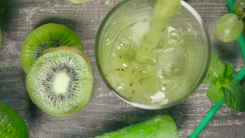 Slow motion fruit kiwi grape smoothie pour into a glass of ice on a background of kiwi grapes and lime top view | Shutterstock HD Video #1014581027