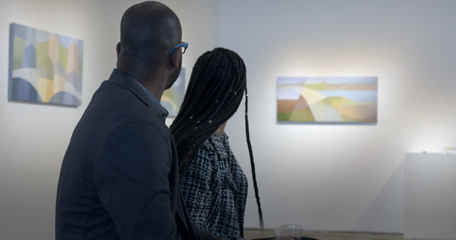 MS African American man and Hispanic woman discuss paintings in gallery during art opening reception. Slider movement with couple in front-sided profile, art soft focus in background #1014581375