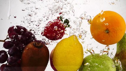 Apple, kiwi, orange, pear, lemon, grape and strawberry falls in water with bubbles. Video in slow motion.