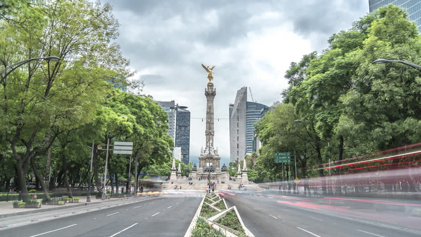 Time lapse of Angel of Independence with traffic in avenue of Mexico City Paseo de la Reforma avenue with cloudy sky, Mexico City, CDMX (Angel de la independencia)