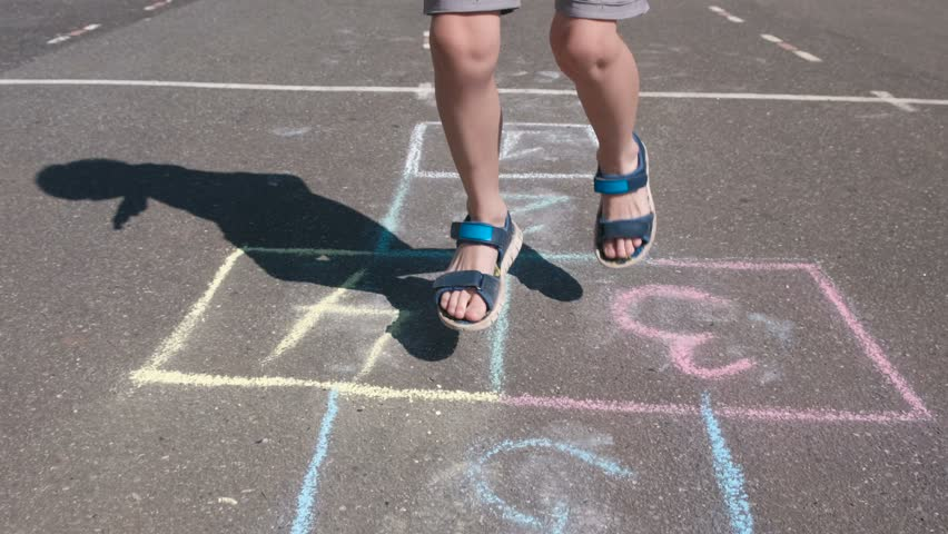 Boy jumps playing hopscotch in the street. Close-up legs. | Shutterstock HD Video #1014590516