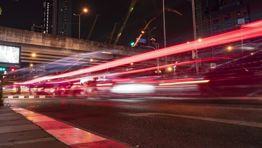Bangkok - August 4: Long exposure time-lapse scene of night traffic with long trail lighting at Rama 9 Intersection on August 4, 2018, in Bangkok, Thailand. | Shutterstock HD Video #1014590534
