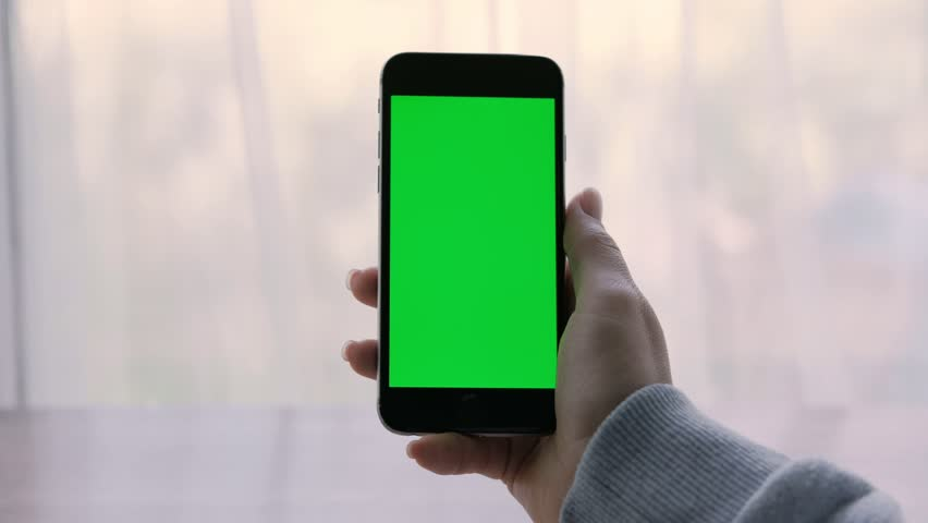 Close-up of a woman's hands holding a smartphone with green screen. Opposite window | Shutterstock HD Video #1014596195