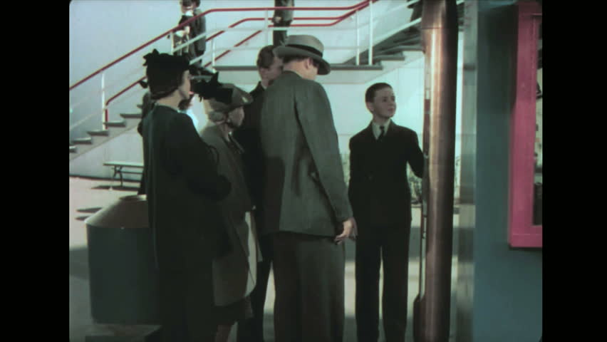 1930s: Family talks around time capsule display. Family observes items inside glass case and talk. | Shutterstock HD Video #1014607388