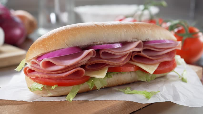 A delicious submarine hoagie sandwich with deli meat, lettuce, tomato, onion and cheese. | Shutterstock HD Video #1014619091