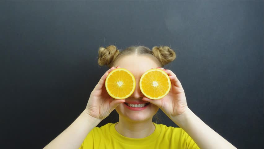 Portrait of beautiful girl with fruits on eyes stop motion loop. Natural food, organic or bio concept.