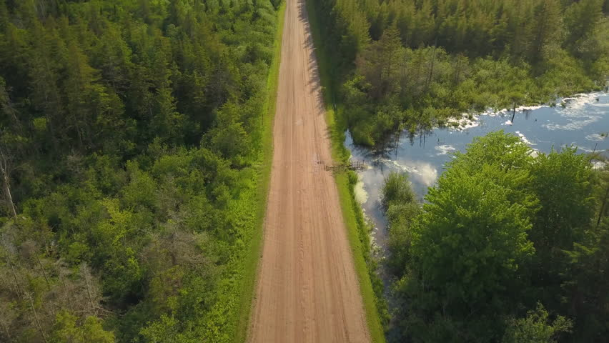 Aerial of white car driving down dirt road towards beautiful farmland #1014623801