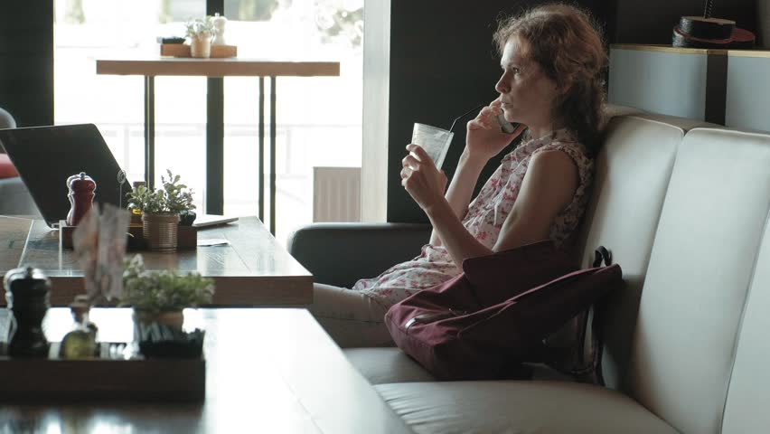 Young business woman sits at a table at a restaurant. She carried a laptop with access to the Internet, it checks the mail and drinking coffee. She looks very happy 4k | Shutterstock HD Video #1014624665