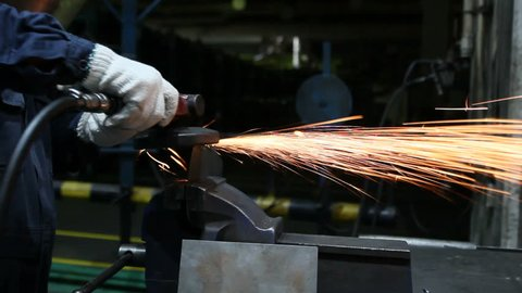 Electric wheel grinding on steel structure in factory.