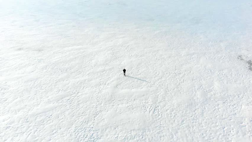 Aerial shot following lone man walking on snowy field in the middle of nowhere. Drone shot of ice tundra with stranded person lost in isolated cold environment. No hope of rescue in snowy disaster. | Shutterstock HD Video #1014628640