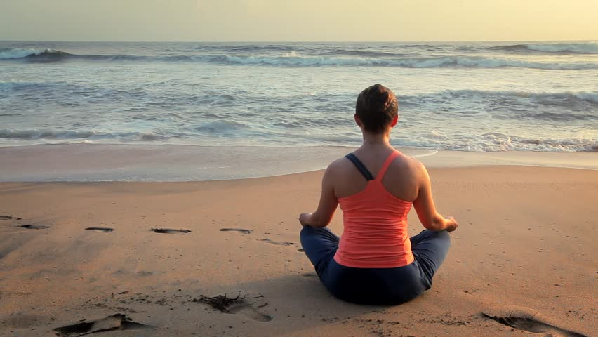 Woman doing yoga - meditate and relax in Padmasana Lotus asana pose with chin mudra outdoors at tropical beach on sunset   Shutterstock HD Video #1014633587