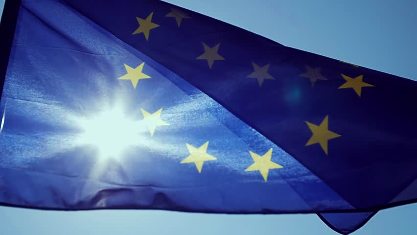 Waving European Union flag in the wind with a blue sky.