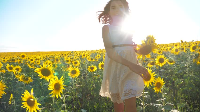 Happy little girl running happy free across the field with sunflowers. slow motion video. smelling big sunflower on summer field. Delight of a pleasant smell. Summer holiday. lifestyle concept