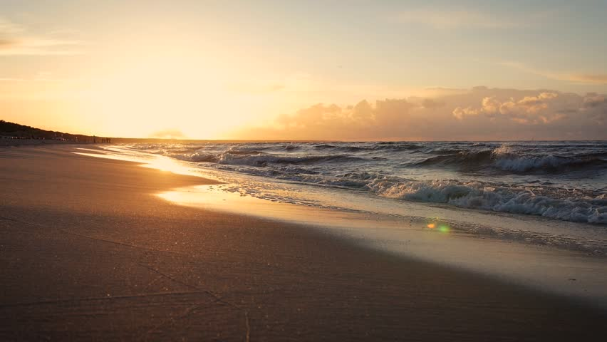 Beautiful sunset on the beach reflected on wet sand with incoming ocean waves in slow motion. Fast moving camera. | Shutterstock HD Video #1014659891