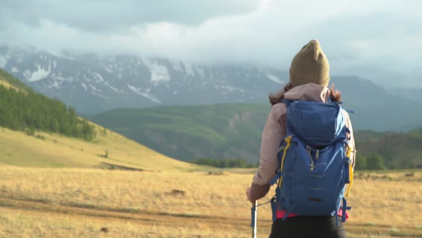 Woman hiking. Hike in the mountains. Woman traveler with backpack on beautiful summer landscape | Shutterstock HD Video #1014659975