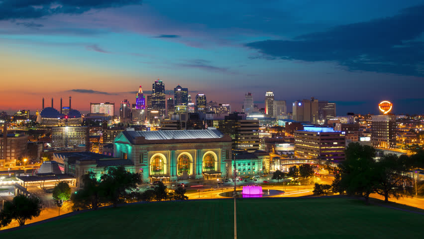 Kansas City Iconic Skyline View in a Vibrant Dusk Setting Overlooking Downtown Skyscrapers with Moving Lights from Buildings and Vehicles under a Colorful Sky