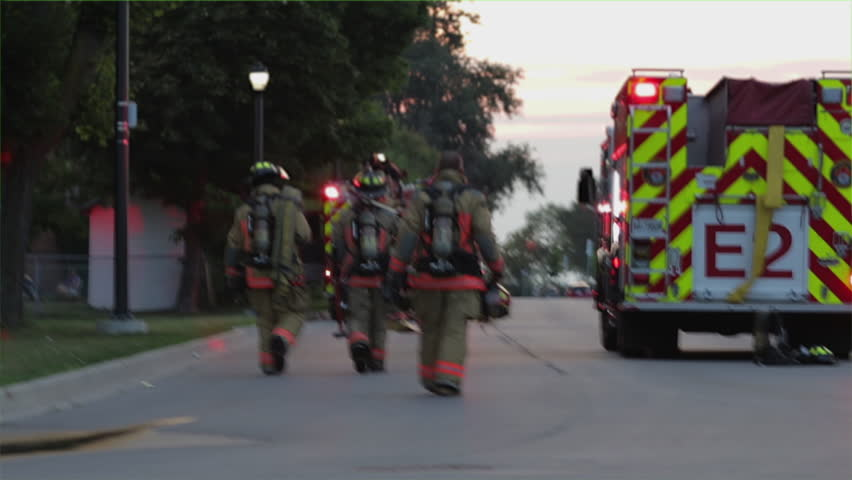Group of firefighters walking towards their firetrucks after an emergency. Fireman in uniforms going back to the fire engines with flashing lights. Teamwork concept of a rescue team of heroes.