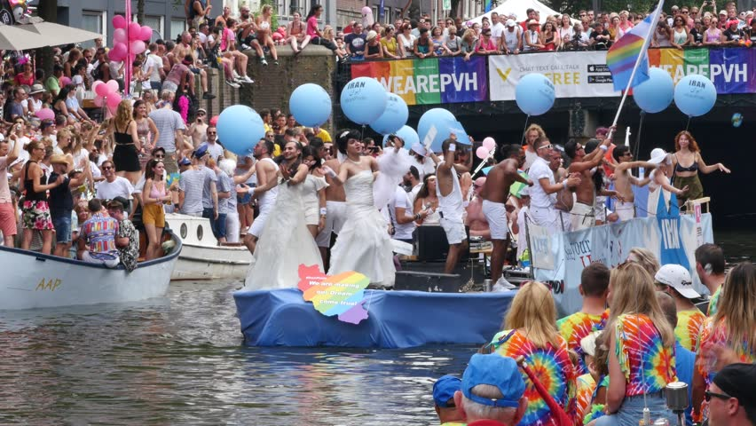 AMSTERDAM, THE NETHERLANDS – AUGUST 4, 2018: Iran refugees boat and visitors at the Canal Gay Parade 2018