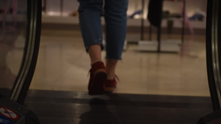 Girl walks off escalator, close up, slow motion #1014688004