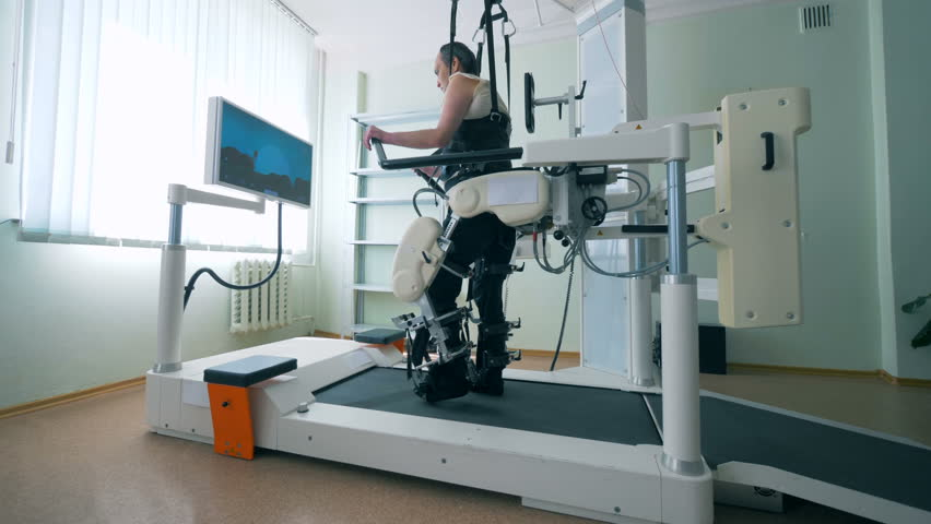 Modern medical recovery device. Training process of a physically challenged man on a walking simulation system