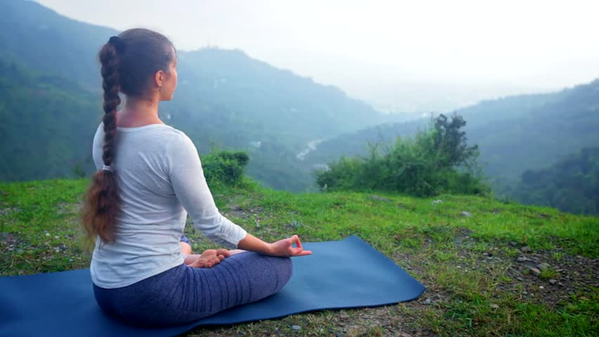 Woman doing yoga - meditating in Padmasana (Lotus Pose) outdoors in mountains on sunset   Shutterstock HD Video #1014692618