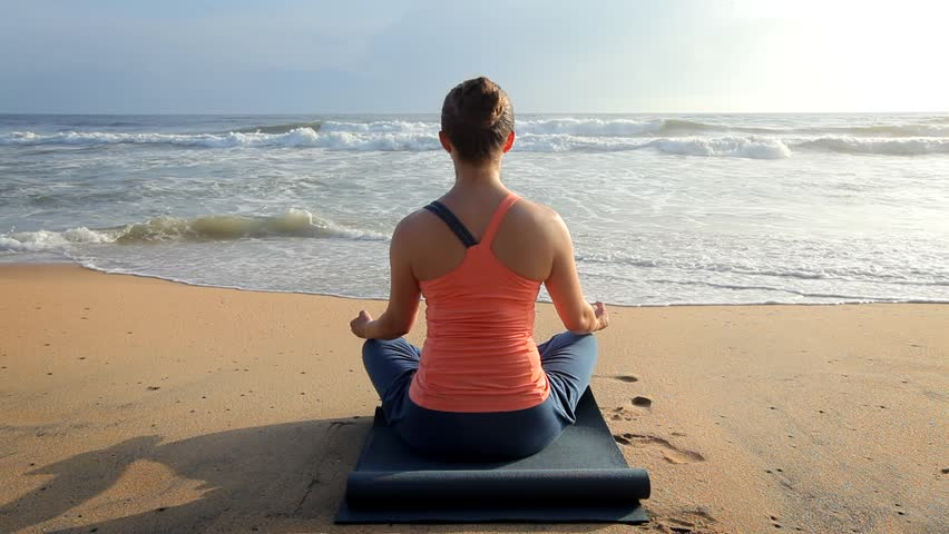 Woman doing yoga - meditate and relax in Padmasana Lotus asana pose with chin mudra outdoors at tropical beach on sunset   Shutterstock HD Video #1014692630